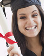 Mixed race graduate in cap and gown holding diploma