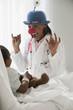 Doctor entertaining girl in hospital bed