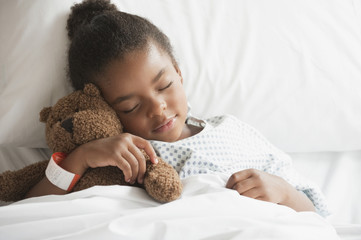 Mixed race girl sleeping in hospital bed with teddy bear
