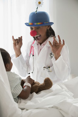 Doctor entertaining girl in hospital bed