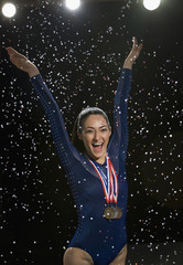 Mixed race gymnast celebrating with medal