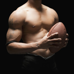 Midsection of bare chested football player