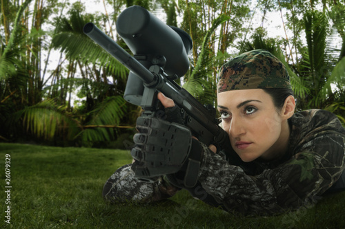 Mixed race woman in combat gear with rifle