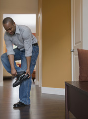 African man putting on shoes