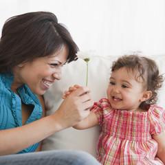 Hispanic mother handing daughter flower
