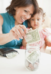 Hispanic mother and daughter saving money