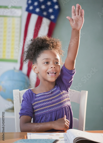 Mixed race girl answering question in classroom