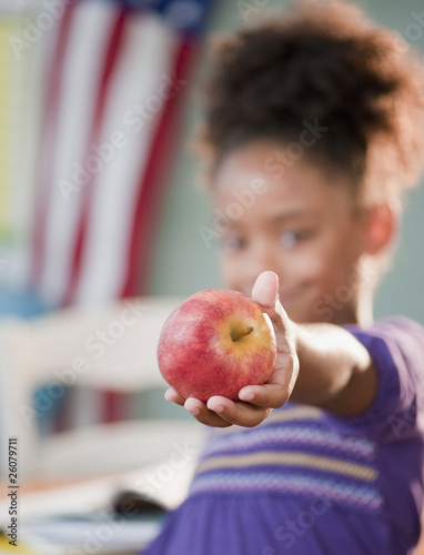 Mixed race girl holding apple