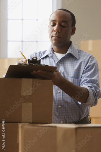 African man with clipboard and moving boxes