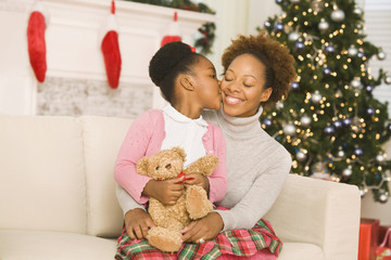 African girl kissing mother at Christmas
