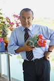 Hispanic businessman holding bouquet of flowers