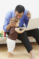 Hispanic father kissing daughter and using laptop