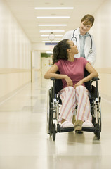 Doctor pushing patient in hospital hallway