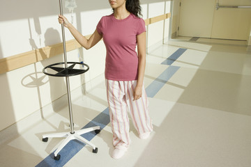 Woman walking down hospital hallway with iv drip