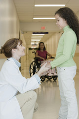 Doctor talking to girl in hospital hallway