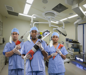 Surgeons holding tools in operating room