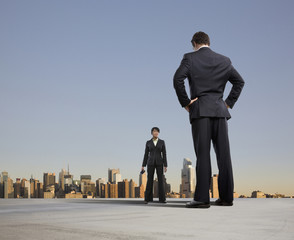 Business people standing on urban rooftop