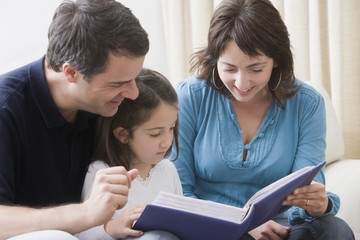 Hispanic parents reading book to daughter