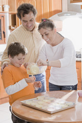 Hispanic family making cupcakes