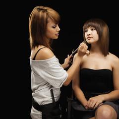 Makeup artist applying makeup to model