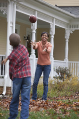 Black mother and son throwing football
