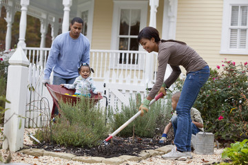"""Black mother, father and daughter gardening"""