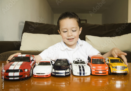 Hispanic boy lining up toy cars