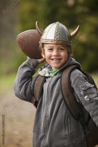 Mixed race boy in viking hat throwing a football