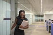 Black businesswoman carrying folder