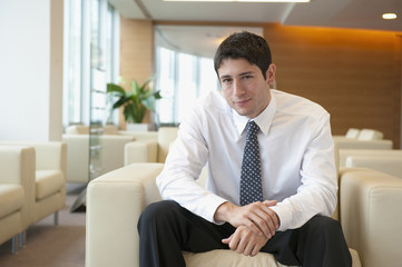 Hispanic businessman sitting in lobby