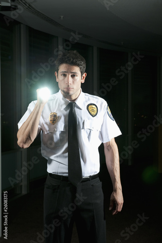 Hispanic security guard checking dark offices