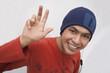 Hispanic man in cap listening to headphones and waving