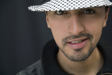 Hispanic man in hat and leather coat