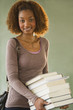 Mixed race woman carrying stack of books
