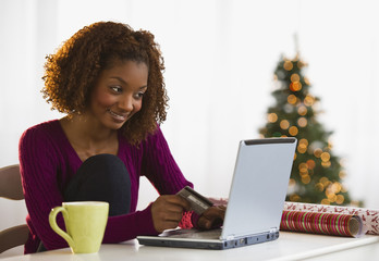 Mixed race woman Christmas shopping on internet with credit card