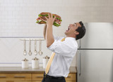 Pacific Islander businessman eating large sandwich