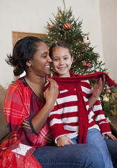 Mixed race mother and daughter hugging near Christmas tree