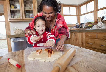 Mixed race mother and daughter baking cookies
