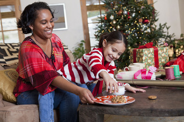 Mixed race mother and daughter eating cookies by Christmas tree