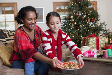 Mixed race mother and daughter leaving cookies by Christmas tree