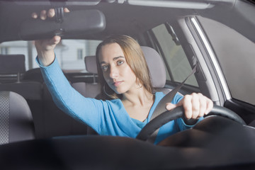Hispanic woman adjusting rearview mirror