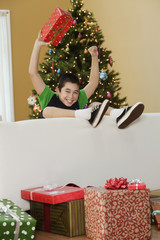 Mixed race boy sitting on couch with Christmas gifts