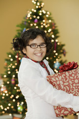 Mixed race girl holding Christmas gift