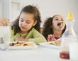Hispanic sisters eating pancakes