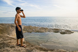 Mixed race boy looking at ocean with binoculars