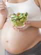 Pregnant Hispanic woman eating salad