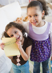Hispanic sisters with Father's Day card