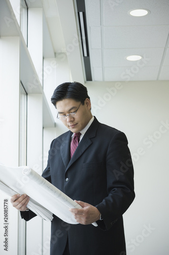 Chinese businessman looking at blueprints