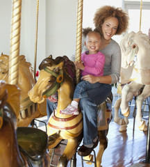 Black mother and daughter riding carousel