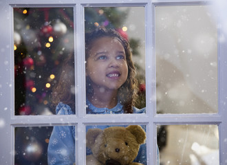 Mixed race girl looking out window at Christmas